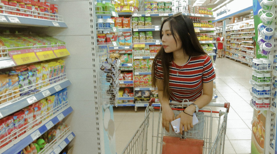 Girl saving money on supermarket